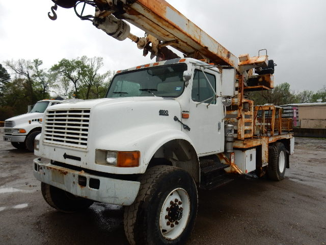 Side front view of white 2001 International 4800 4x4 Digger
