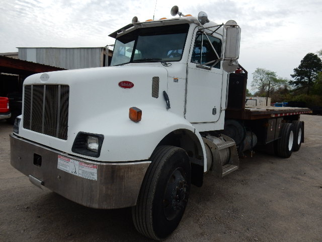 Side front view of white 2004 model Peterbilt flatbed truck tractor for sale in Channelview, Tx